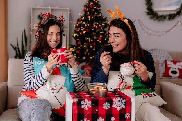 Uśmiechnięte ładne młode dziewczyny z wieńcem z ostrokrzewu i opaską z renifera trzymają kubki siedząc na fotelach i ciesząc się świątecznym czasem w domu