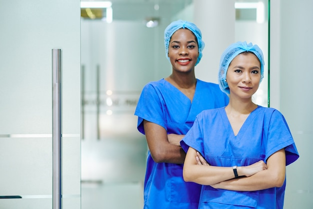 Uśmiechnięte ładne wieloetniczne pielęgniarki medyczne w fartuchach i jednorazowych czepkach stoją na szpitalnym korytarzu
