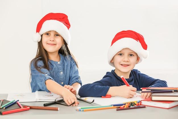 Uśmiechnięte małe dzieci przy stole, rysowanie kredkami w santa hat