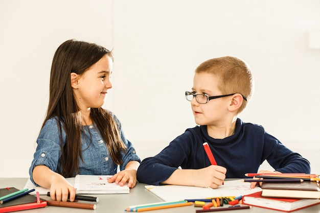 Uśmiechnięte małe dzieci przy stole rysowanie kredkami