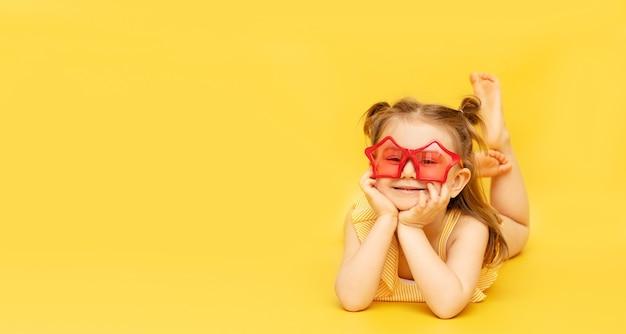 Uśmiechnięte małe dziecko dziewczynka ubrana w strój kąpielowy i czerwone śmieszne okulary leżące na żółtej ścianie