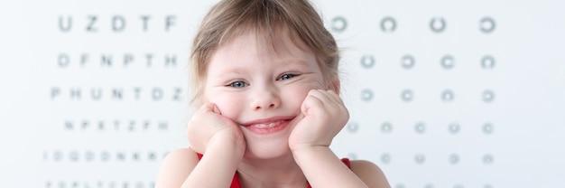 Uśmiechnięte małe dziecko na stole do badania wzroku w portretie kliniki medycznej