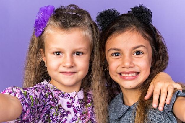 Uśmiechnięte małe ładne dziewczyny odizolowane na fioletowej ścianie z miejscem na kopię