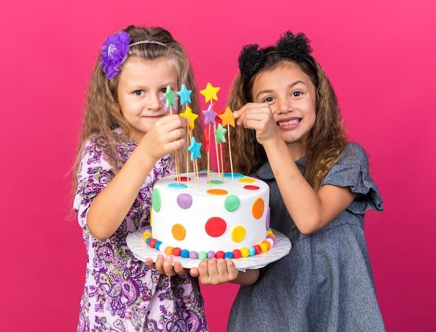 Uśmiechnięte małe ładne dziewczyny trzymające razem tort urodzinowy na różowej ścianie z miejscem na kopię