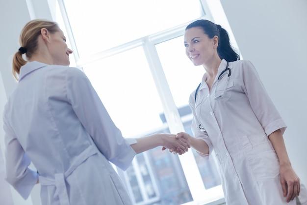 Uśmiechnięte, miłe młode pielęgniarki stojące w klinice i cieszące się rozmową podczas uścisku dłoni