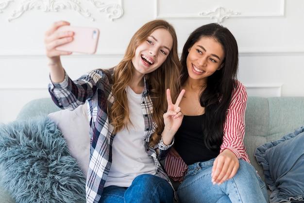 Uśmiechnięte młode kobiety bierze selfie na telefonie