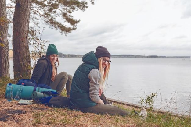 Uśmiechnięte młode kobiety odpoczywa podczas podróżować blisko jeziora