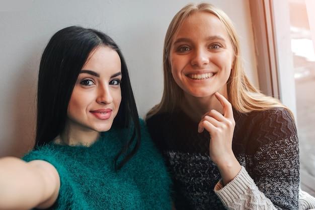 Uśmiechnięte młode kobiety robiące selfie podczas picia kawy w pomieszczeniu na spotkaniu lunchowym