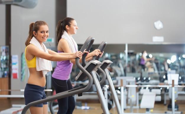 Uśmiechnięte młode kobiety używa karuzelę biegać w gym