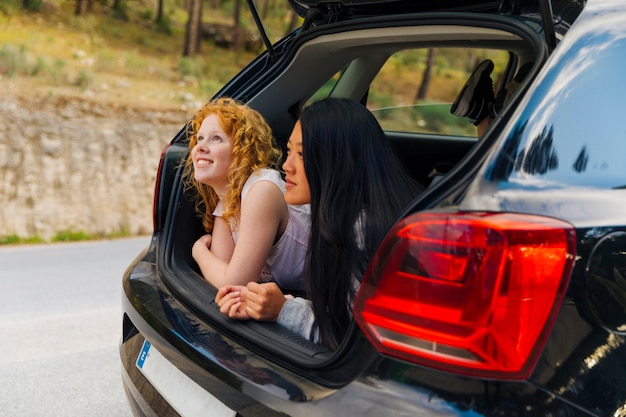 Uśmiechnięte młode kobiety w otwartym samochodowym bagażniku