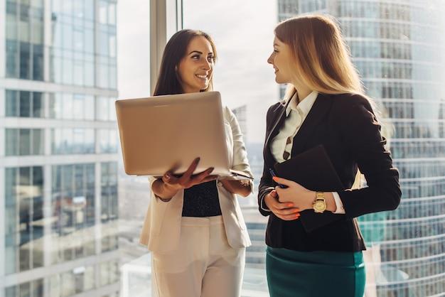 Uśmiechnięte młode kobiety z laptopa stojąc i rozmawiając w biurze.