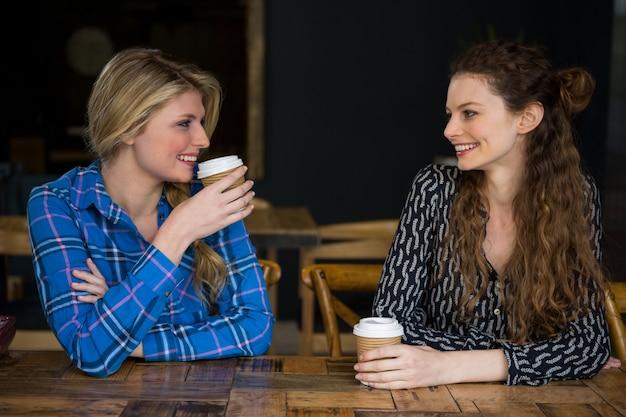 Uśmiechnięte młode koleżanki o kawie podczas rozmowy w kawiarni