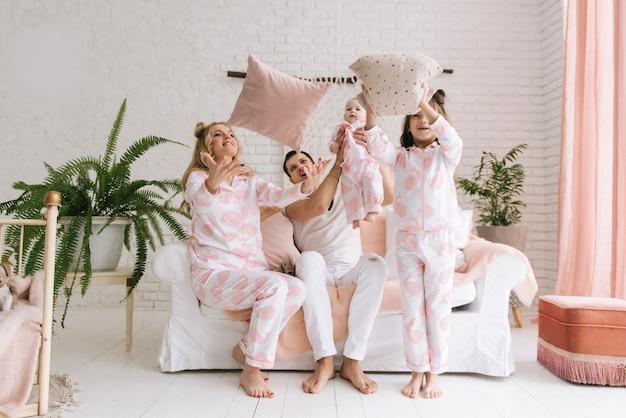 Uśmiechnięte młode rodzice, ich dwie córki bawią się w domu i rzucają poduszkami w jasne wnętrze