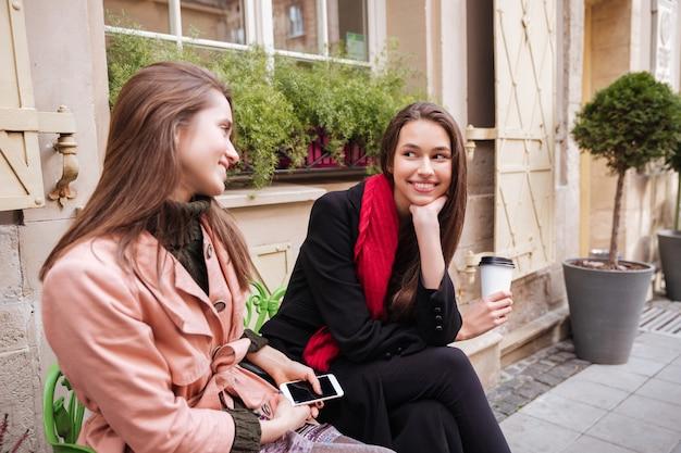 Uśmiechnięte modelki w płaszczach siedzą. na ulicy