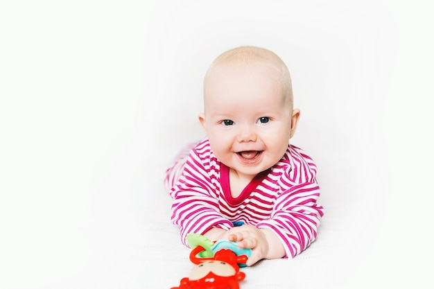 Uśmiechnięte najsłodsze dziecko bawiące się kolorowymi zabawkami szczęśliwe 6-miesięczne dziecko bawiące się i odkrywające