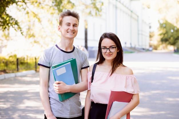 Uśmiechnięte nastolatki stojąc w kampusie studenckim w słoneczny dzień, trzymając materiały do nauki i uśmiechając się