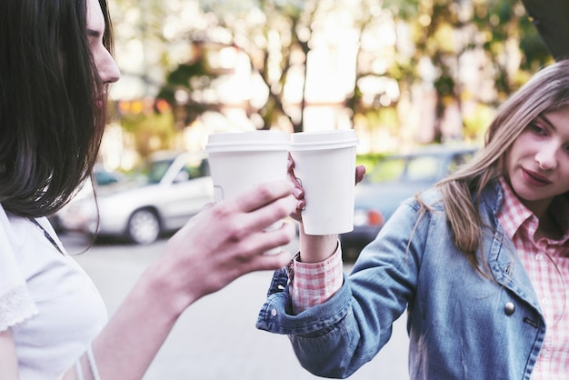 Uśmiechnięte nastoletnie dziewczyny z filiżanek na ulicy. koncepcja napojów i przyjaźni.
