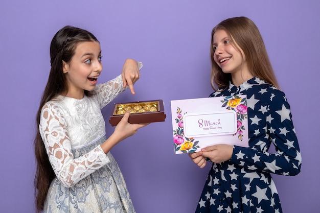 Uśmiechnięte patrząc na siebie dwie małe dziewczynki na szczęśliwy dzień kobiet trzymające kartkę z życzeniami z pudełkiem cukierków