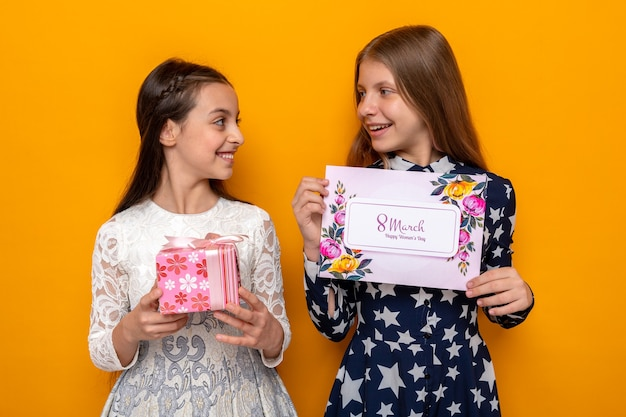 Uśmiechnięte patrząc na siebie dwie małe dziewczynki na szczęśliwy dzień kobiet trzymające prezent z kartką z życzeniami