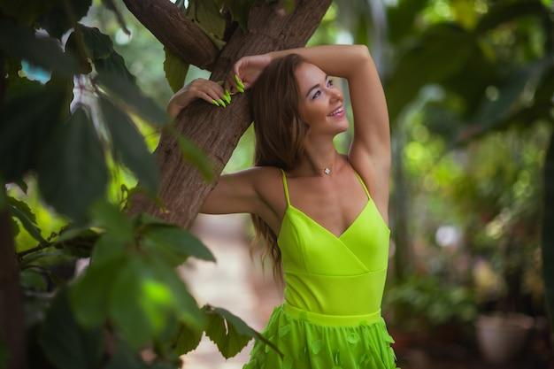 Uśmiechnięte piękno w ogrodzie patrząc na kamerę
