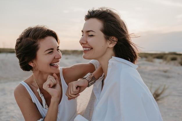 Uśmiechnięte przyjaciółki dwóch młodych kobiet zabawy na plaży o zachodzie słońca, wesoły lesbijski romans kochają