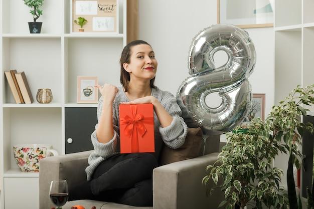 Uśmiechnięte punkty z boku piękna dziewczyna w szczęśliwy dzień kobiet trzymająca prezent siedzący na fotelu w salonie
