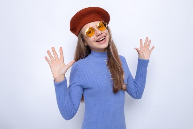 Uśmiechnięte rozkładające się ręce piękna mała dziewczynka w okularach z kapeluszem na białej ścianie