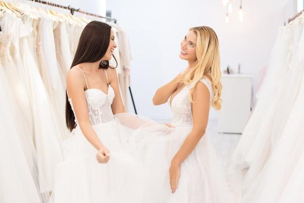 Uśmiechnięte rozmarzone młode panny młode w sukniach ślubnych rozmawiają o dniu swojego ślubu podczas dopasowywania sukienek w sklepie