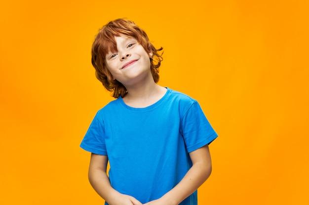 Uśmiechnięte rudowłose dziecko przechyliło głowę na bok na żółto