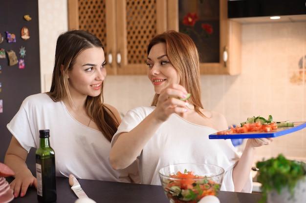 Uśmiechnięte siostry przygotowywa obiad w kuchni wpólnie