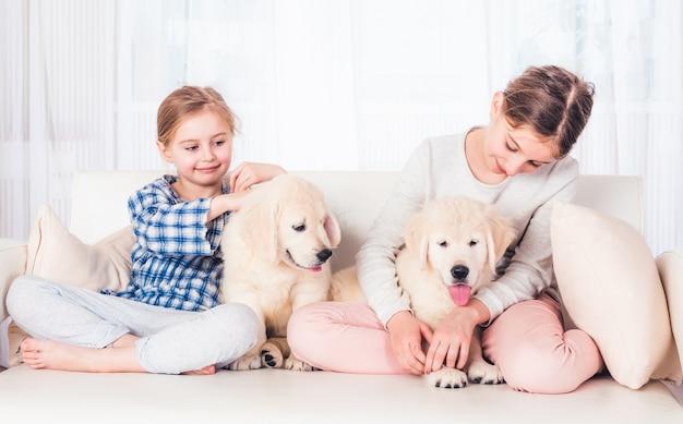 Uśmiechnięte siostry siedzi ze szczeniakami
