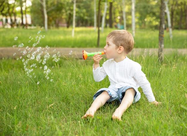 Uśmiechnięte śmieszne dziecko bawi się bańkami mydlanymi. dziecko dmuchanie bańki mydlanej