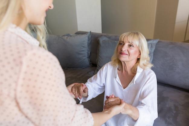 Uśmiechnięte starsze kobiety mienia ręki z jej wnuczką