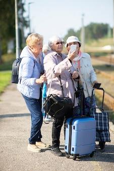 Uśmiechnięte starsze kobiety robią sobie autoportret na peronie czekając na pociąg do podróży