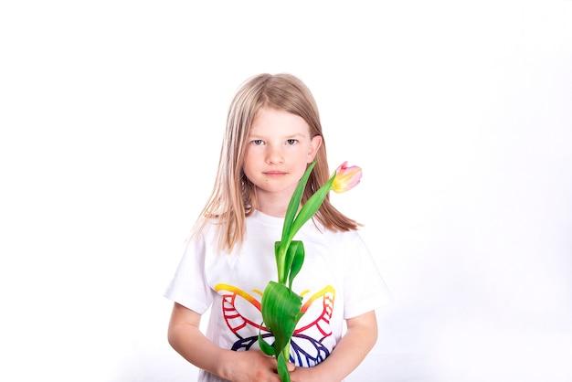 Uśmiechnięte szczęśliwe dziecko dziewczynka trzyma twarz kwiatu tulipana na białej powierzchni