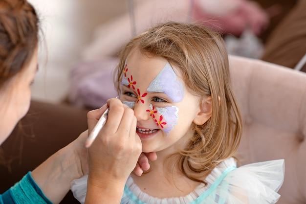 Uśmiechnięte szczęśliwe dziecko z twarzą art aqua grimm na urodziny lub halloween party malowanie twarzy