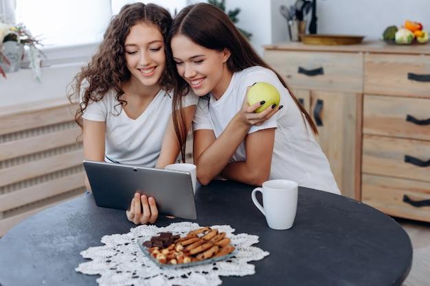 Uśmiechnięte szczęśliwe dziewczyny ogląda śmieszne filmy na tablecie, jedna z dziewcząt trzyma jabłko w dłoniach