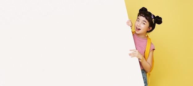 Uśmiechnięte szczęśliwe słodkie azjatyckie dziecko chowa się za pustą białą deską na białym tle na żółtej ścianie.