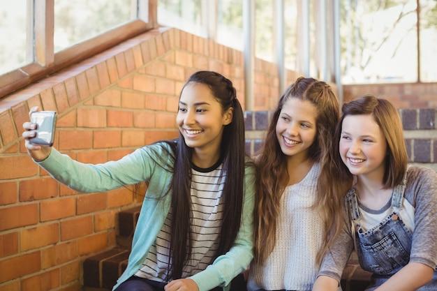 Uśmiechnięte uczennice siedzą na schodach biorąc selfie z telefonem komórkowym