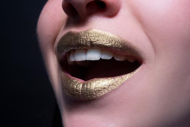 Uśmiechnięte usta zbliżenie sexy piękne kobiece złote usta izolowane złota szminka