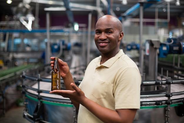 Uśmiechniętego pracownika fabrycznego mienia pusta butelka