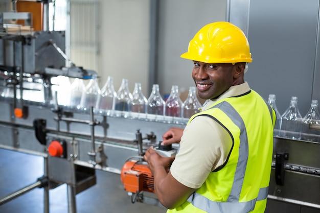 Uśmiechniętego pracownika fabrycznego operacyjna maszyna w fabryce