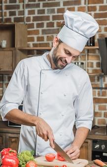 Uśmiechniętego profesjonalisty kucharza tnący warzywa w kuchni