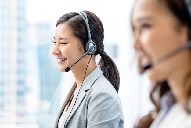 Uśmiechniętego telemarketingu azjatycka kobieta pracuje w centrum telefonicznego biurze