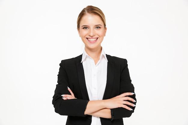 Uśmiechniętej blondynki biznesowa kobieta pozuje z krzyżować rękami