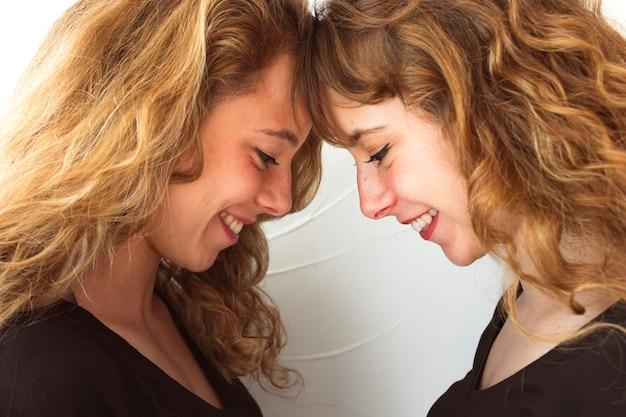 Uśmiechniętej blondynki młoda siostra dotyka ich czoło