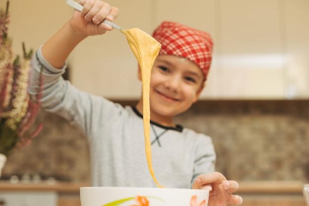 Uśmiechniętej chłopiec kulinarny ciasto dla ciasta