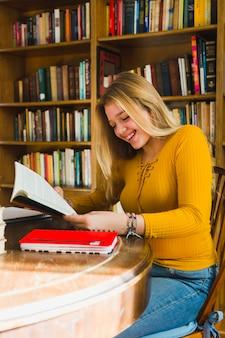 Uśmiechniętej dziewczyny czytelnicza książka w bibliotece