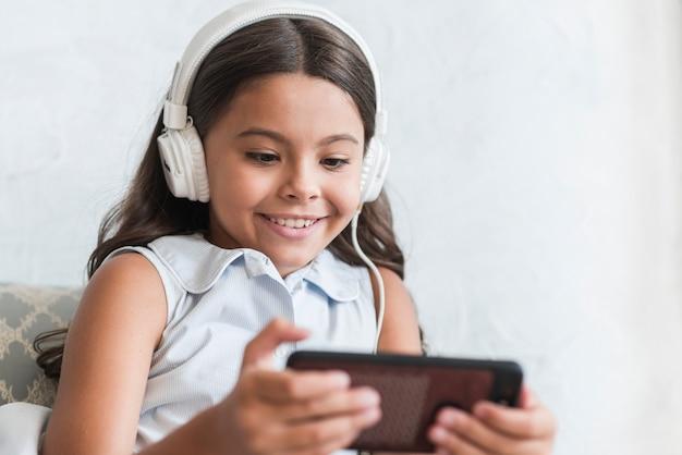 Uśmiechniętej dziewczyny słuchająca muzyka na hełmofonie używać mądrze telefon