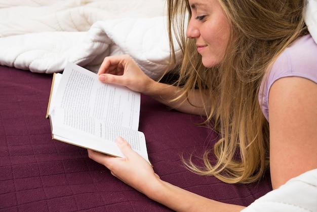 Uśmiechniętej młodej blondynki kobiety czytelnicza książka na łóżku